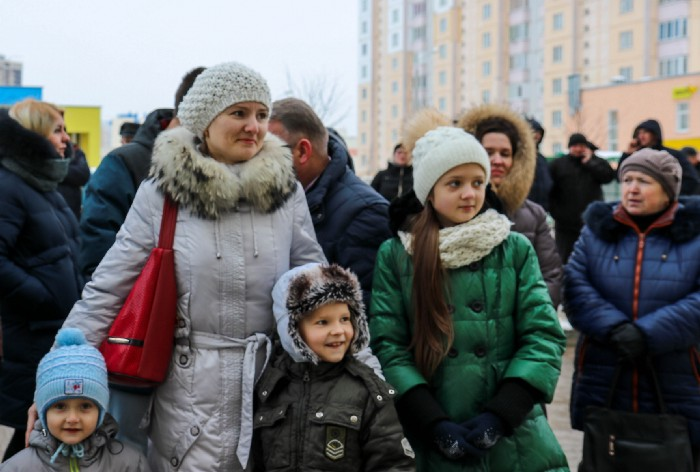 A mother and her two daughters in a crowd outside on a cold day
