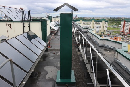 A roof of a large apartment building with solar panel rigs on it
