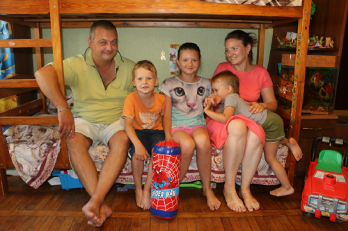A family of 5 sitting on the bottom level of a bunk bed