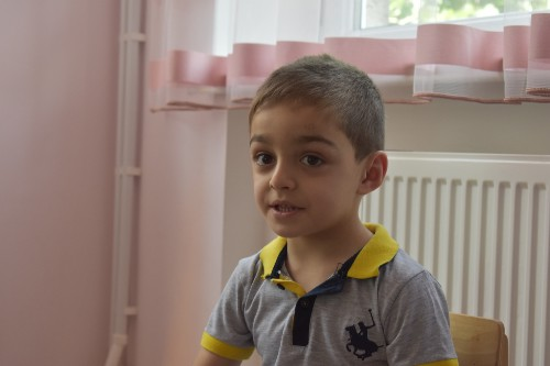 A small boy in a grey t-shirt sitting on a chair at school