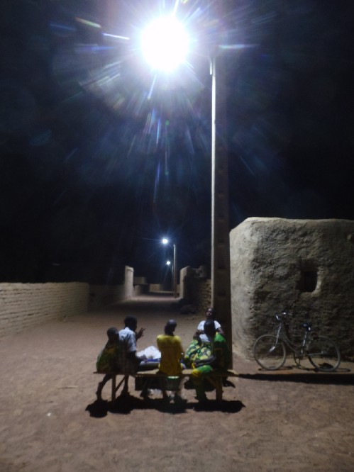 5 people sitting on a rural street under a light post