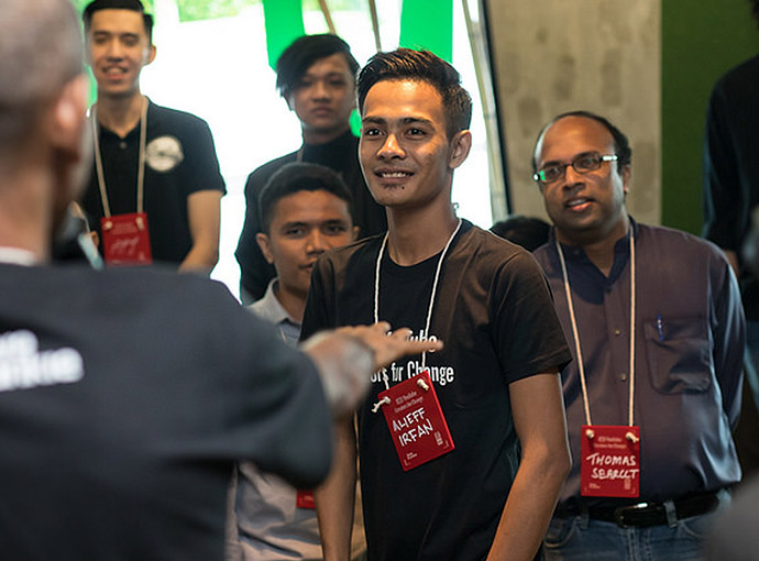 A young man at a conference smiling in a crowd