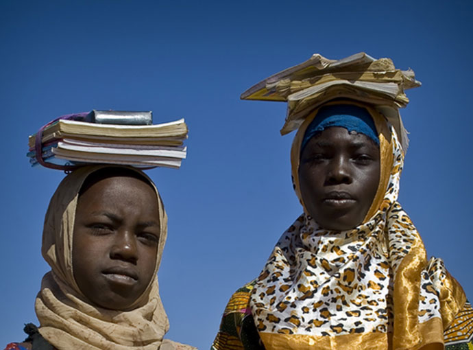 Two girls carrying schoolbooks that are balanced on their heads with a carrying contraption