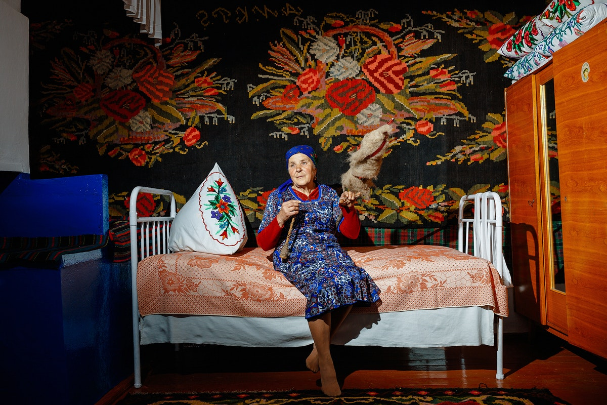 An elderly woman sitting in a colourful room on a bed