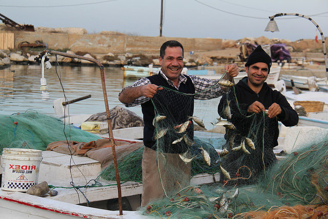 Local fishermen holding a large fishing net celebrating their catch
