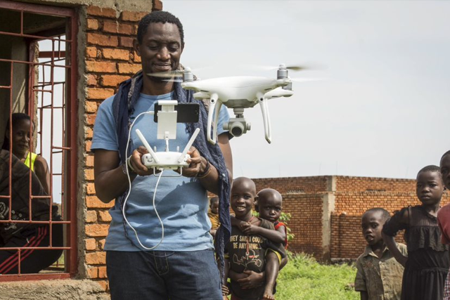 A man standing around a group of children controlling a drone