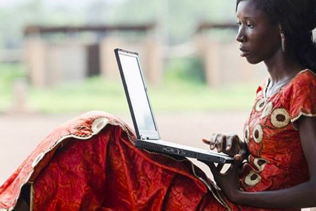 A woman sitting in a village on a laptop computer